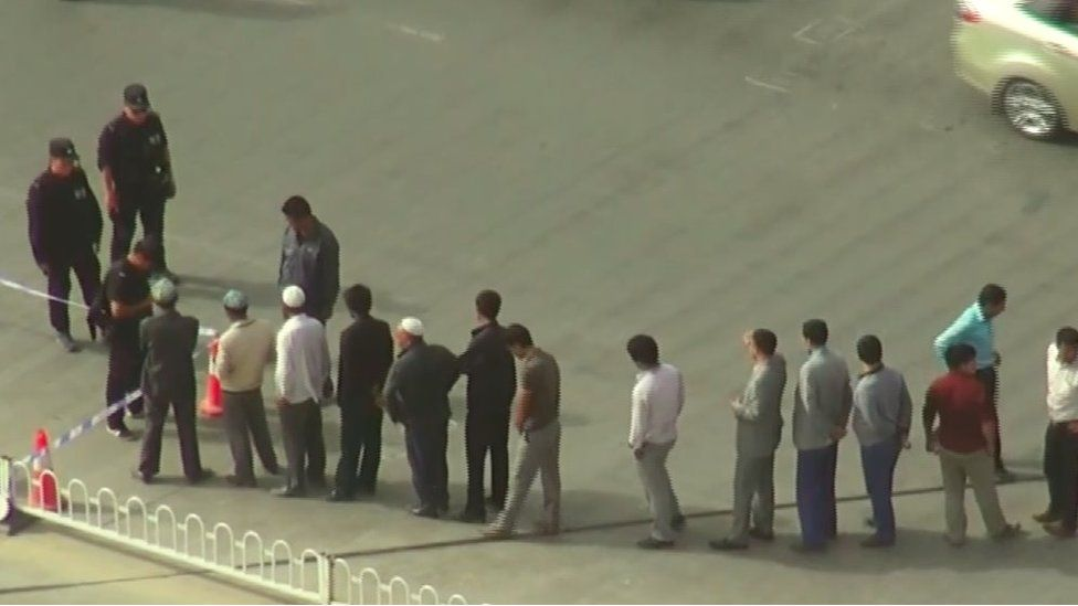 A line of local men waiting in line to be searched by the police