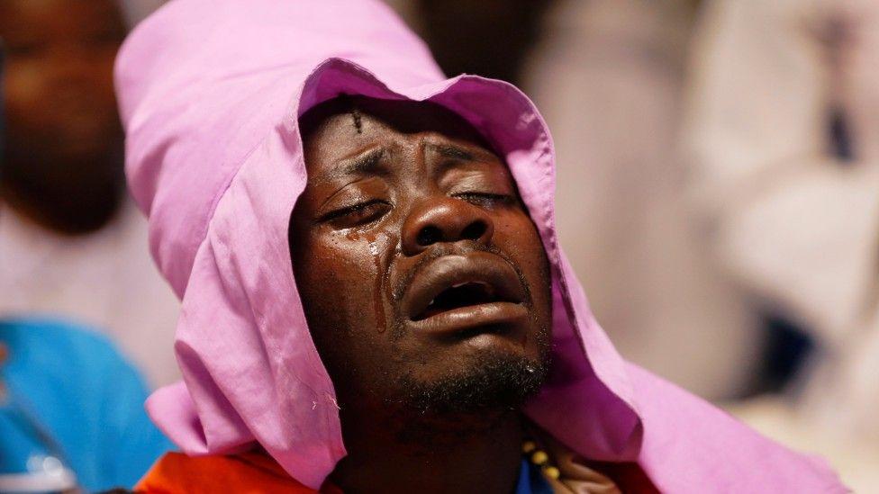 A man cries during mass in Kibera, Nairobi, Kenya - Sunday 22 March 2020