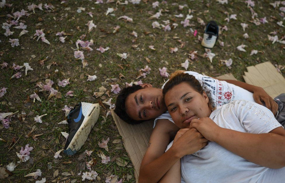"""Central American migrants - taking part in a caravan called """"Migrant Viacrucis""""- rest at a sports centre field."""