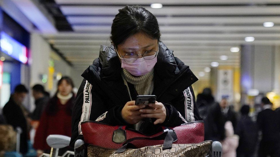 A passenger arrives wearing a mask at Terminal 4, Heathrow Airport, London