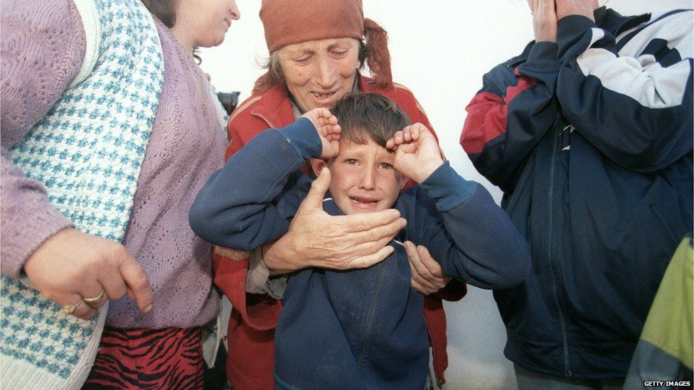 A picture taken on March 7, 1998 shows an elderly ethnic Albanian refugee woman from the village of Donje Prekaze crying as she holds her grandson while hiding from Serbian police in a house in the forest near their village