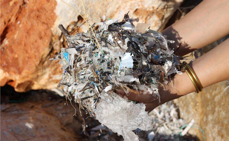 Washed-up plastic gathering between rocks on Paros