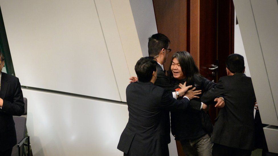 Leung Kwok-hung, Known as 'Long Hair' (R), is removed from the Legislative Council Chambers for interjecting during Chief Executive Leung Chun-ying 2016 Policy Address in the Admiralty district of Hong Kong on January 13, 2016