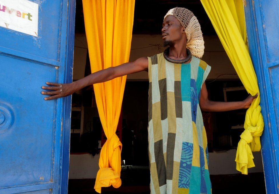 A man stands at the entrance to a community shop. He is wearing bright clothes that match the curtains and doors.