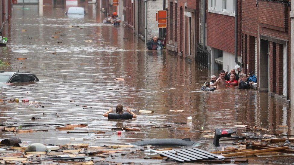 A woman tries to move in a flooded street in Liège, Belgium