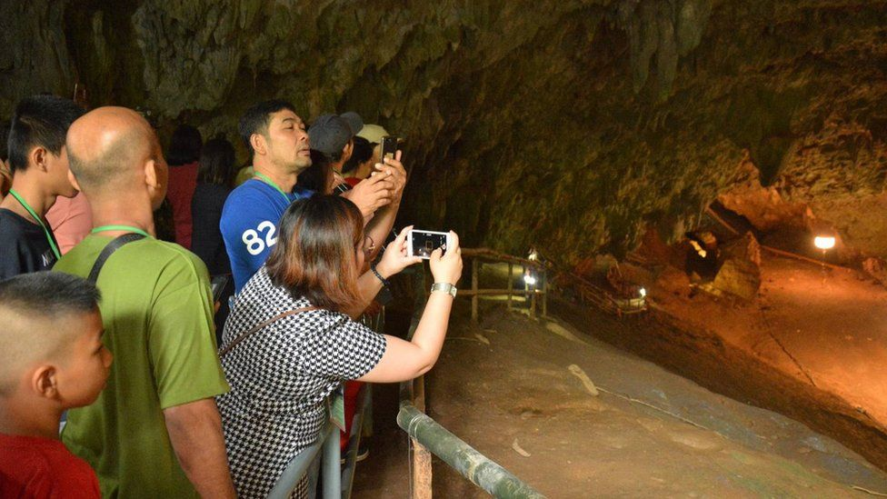 People take photographs at the entrance of the Tham Luang cave in Mae Sai district, Chiang Rai province, Thailand, on 01 November 2019.