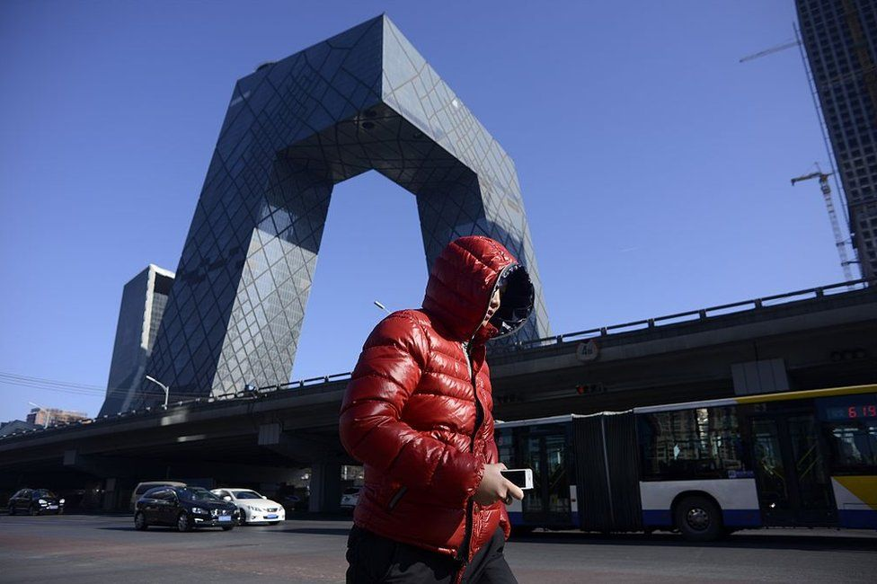 A man walks down the street as the CCTV Tower looms in the background in the central business district in Beijing on 20 January 2017.