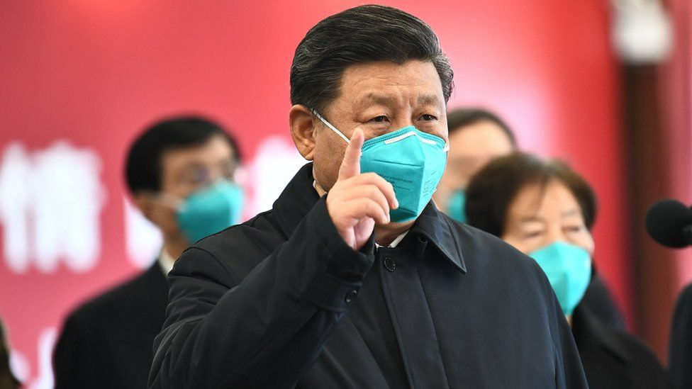 Chinese President Xi Jinping wearing a mask as he GESTURES to a coronavirus patient and medical staff via a video link at the Huoshenshan hospital in Wuhan