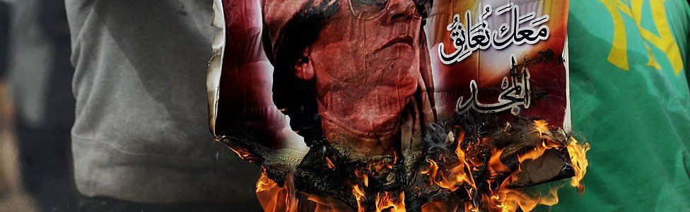 Man holding a burning poster of Muammar Gadaffi