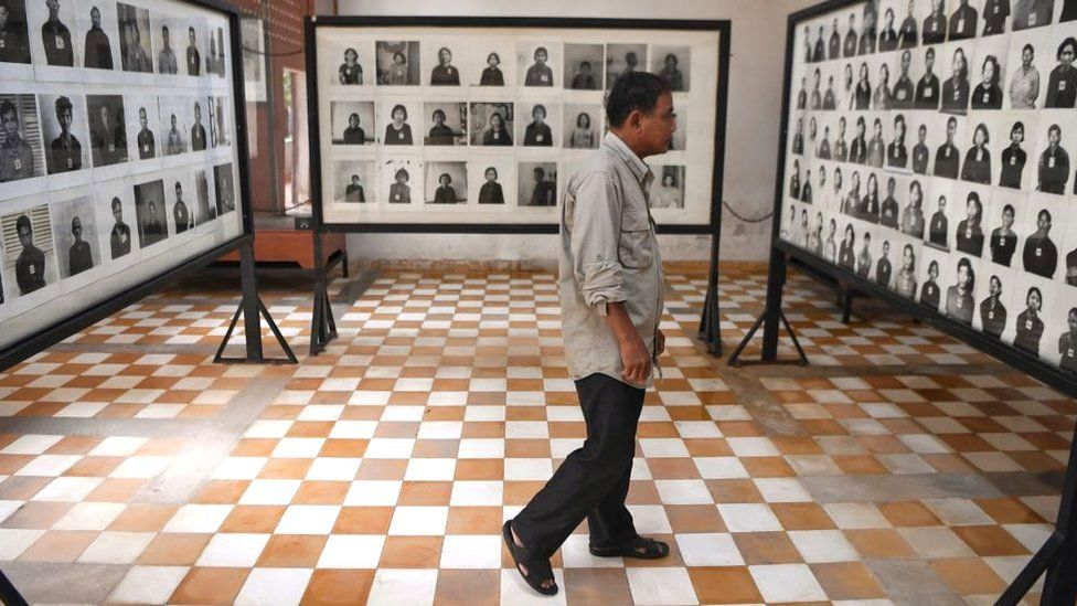 A man looks at photographs of victims at the Tuol Sleng genocide museum in Phnom Penh