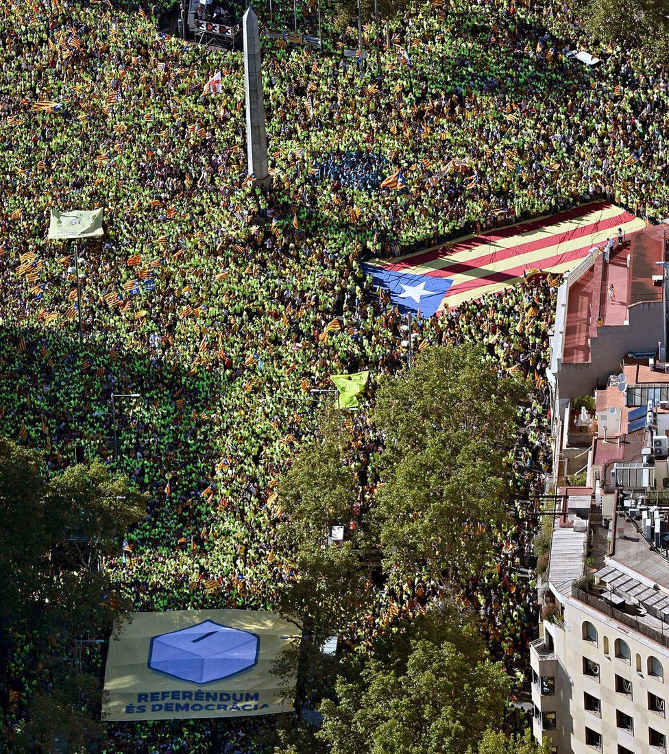 """An aerial view of people waving a giant """"Estelada"""" (pro-independence Catalan flags) and a giant banner reading in Catalan """"Peace"""" during a pro-independence demonstration, on September 11, 2017"""