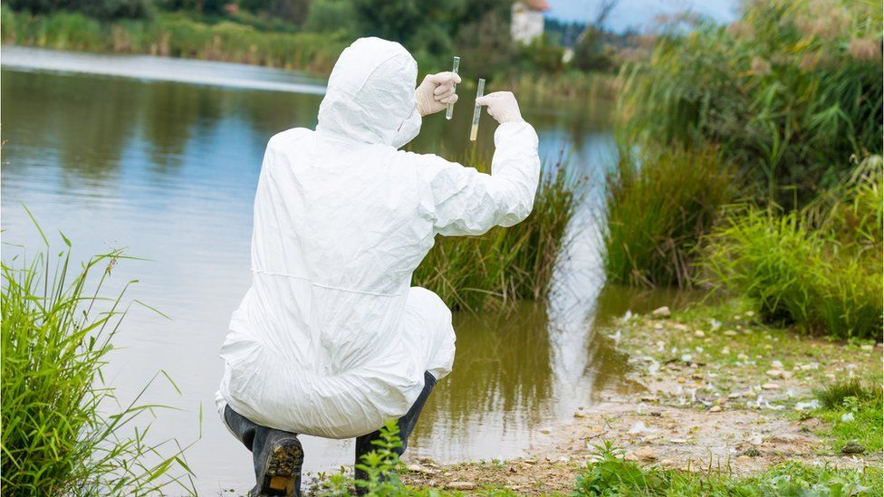 Person holding up water samples next to lake
