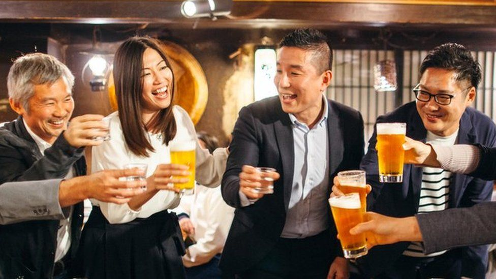 Group of Japanese people toast with drinks at a restaurant