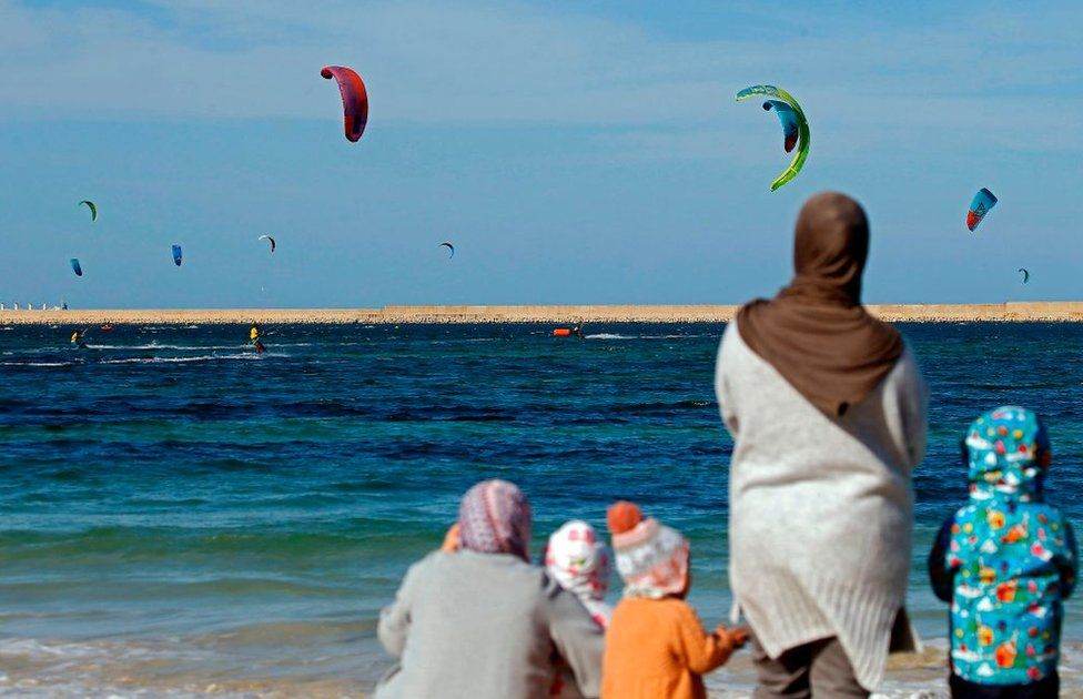 Women and children watch a kite surfing tournament.