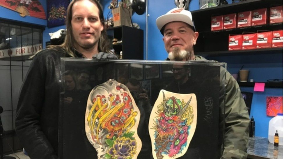 Tattoo artists Kurt Wiscombe (left) Clint Danroth with the preserved tattoos they did for Chris Wenzel