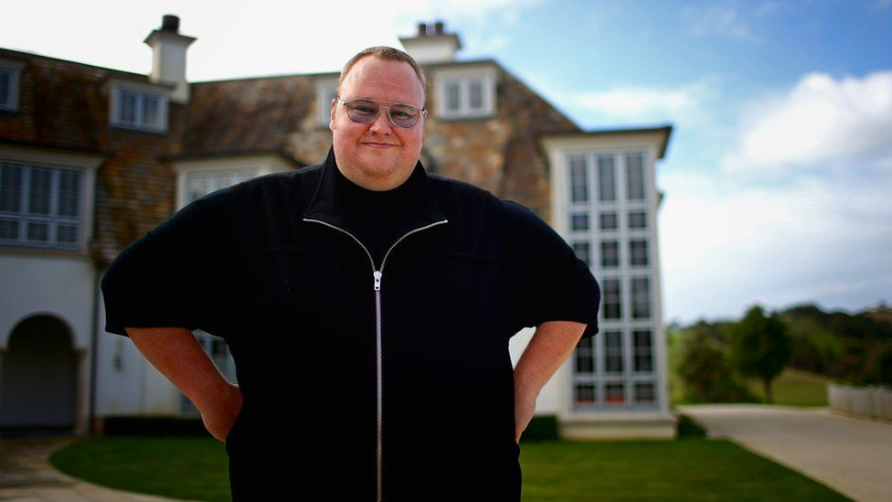 Kim Dotcom stands outside his mansion in New Zealand