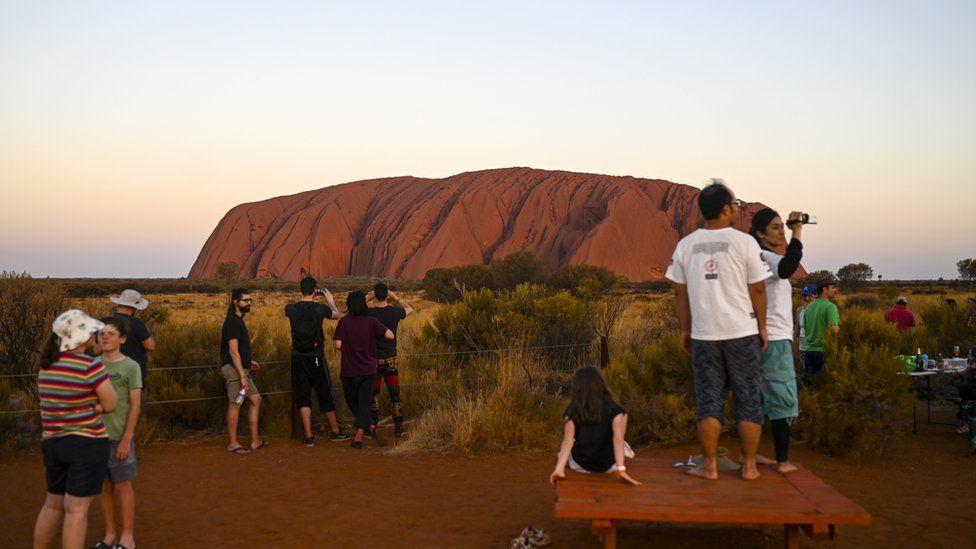 Tourists gather to watch Uluru at sunset