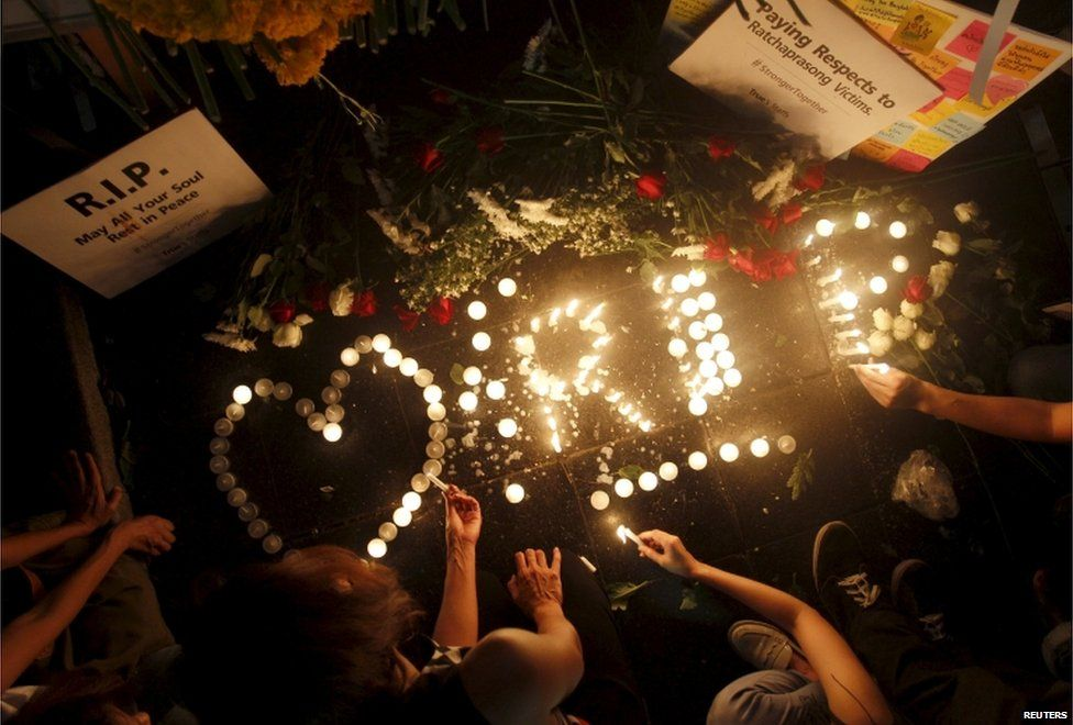 People light candles at the Erawan shrine, the site of Monday's deadly blast, in central Bangkok, Thailand, 18 August 2015.