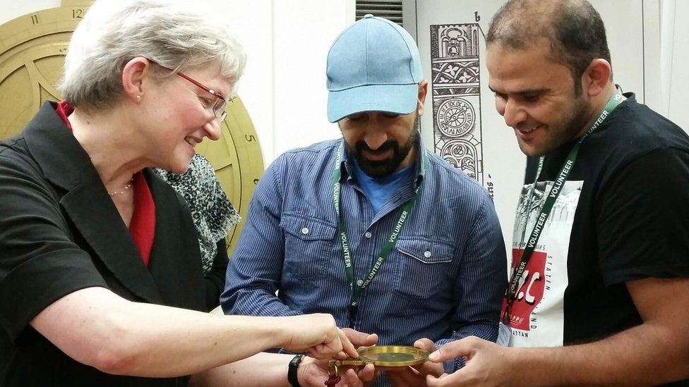 Volunteers Tammam and Abdullah examine an astrolabe with museum director Silke Ackermann
