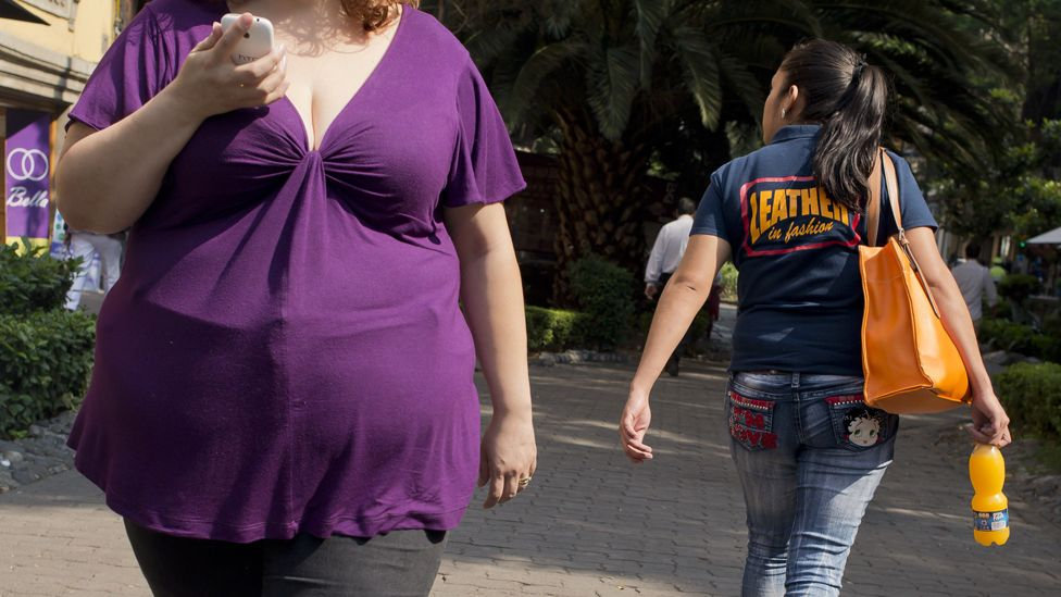 Obese woman, and woman holding soft drink, Mexico