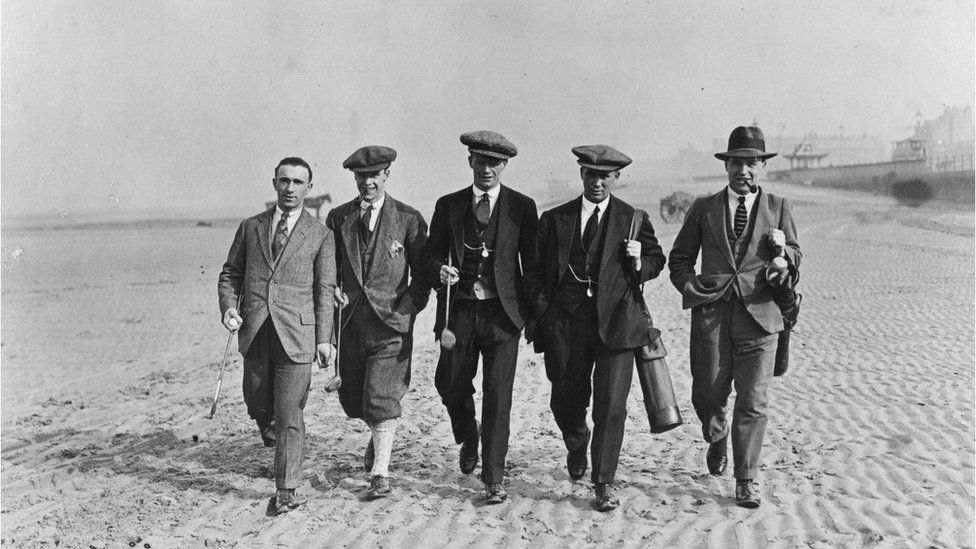 March 1923: Five members of the Sheffield United football team players walk along the beach carrying golf clubs