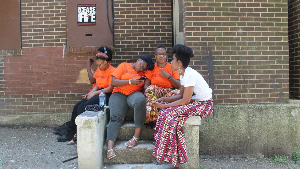 Erricka Bridgeford, right centre, sits with her friend Ellen Gee, right, and her children outside of an abandoned rowhouse