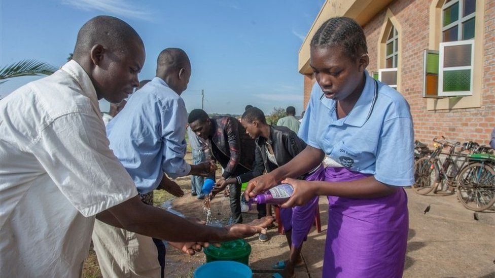 Parishioners wash hands as a preventive measure against the spread of Covid-19 on the last day of full gatherings as a parish at the Saint Don Bosco Catholic Parish in Lilongwe on March 22, 2020