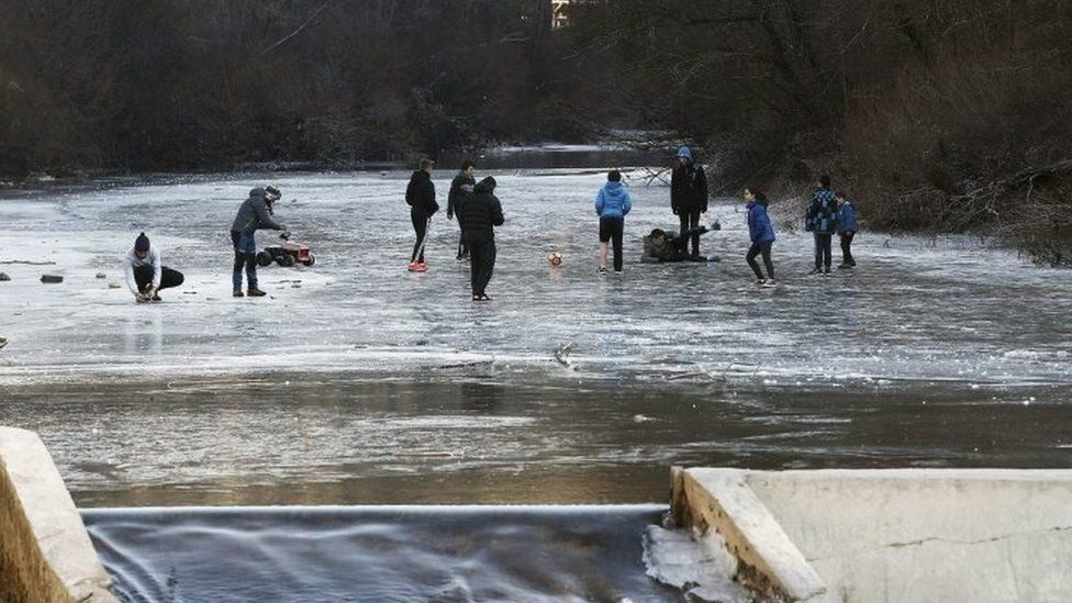 Youngsters play on a ice-covered section of the Esca river in Burgui, Navarra province, Spain. Photo: 9 January 2017