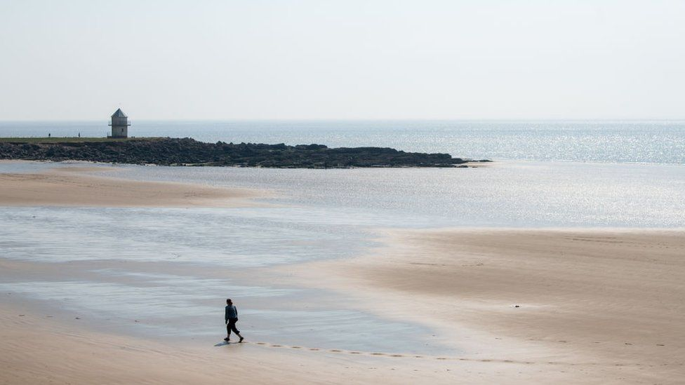 A woman walks alone on Trecco Bay Beach, in Porthcawl, Wales