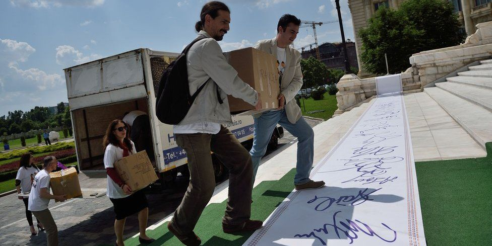 Volunteers unload dozens of boxes from a truck, crossing an oversized roll of giant signatures as they climb the senate steps in Bucharest