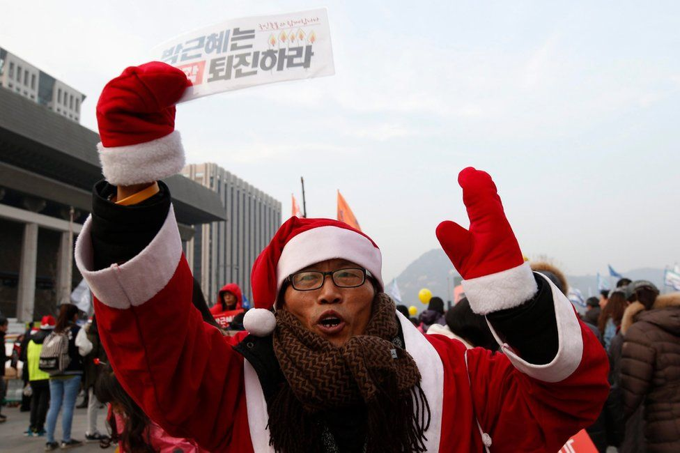 """A South Korean wearing a Santa Claus costume, shouts slogans while carrying placard reading """"Park Geun-Hye and Prime Minister Hwang Kyo-ahn Out"""" during a rally against president Park Geun-hye on the Gwanghwamun Square in Seoul, South Korea, 24 December 2016."""