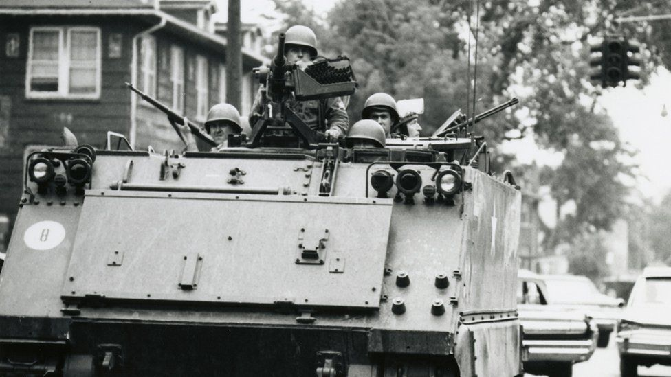 An image of a US Army tank patrolling through the streets of Detroit in 1967.