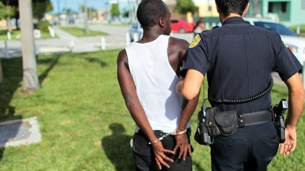 A police officer walks a handcuffed person to a patrol car in Miami, Florida - 11 August 2010