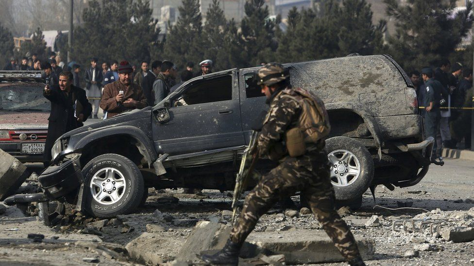In this 28 December 2016 image Afghan security personnel inspect the site of roadside bomb blast in Kabul, Afghanistan