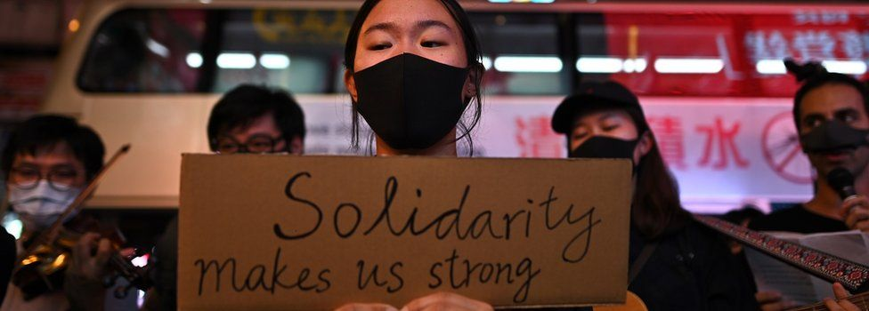 """A protester holds up a sign saying """"Solidarity makes us strong"""" during the protests- October 23rd 2019."""