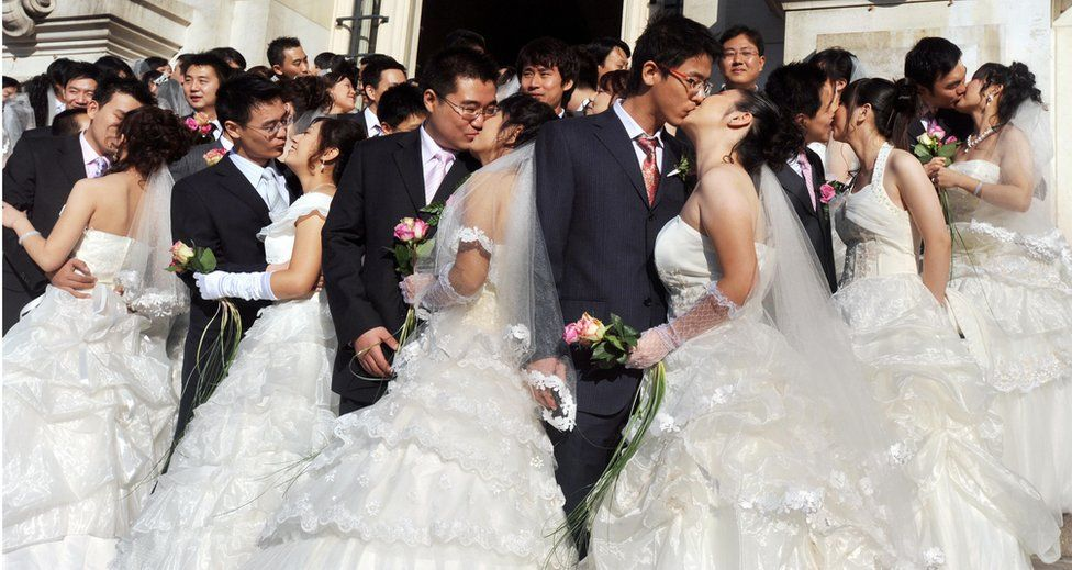 Newly-wed young Chinese couples kiss in front of the Tours city hall, in France Loire's Valley on October 10, 2008, after a wedding ceremony celebrated by the city's mayor.