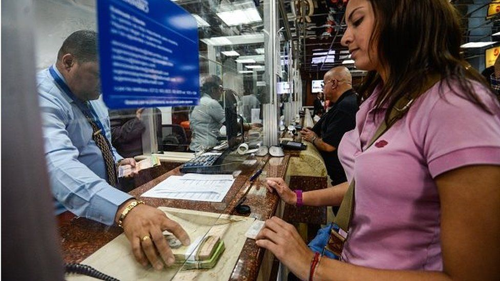 People queue at a currency exchange office in Caracas on 19 February, 2015.