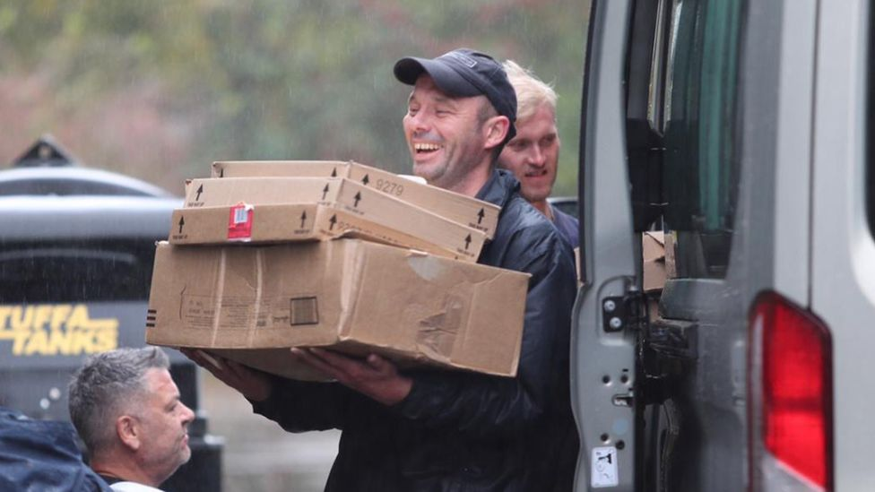 Man holds boxes in rain