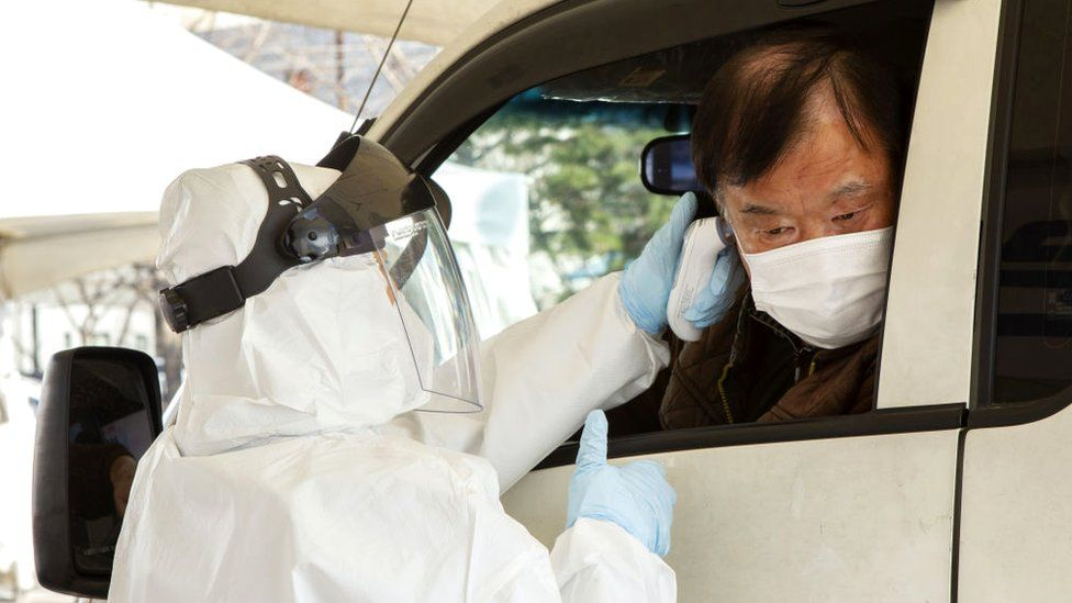 People are getting checked in their vehicles at a drive-through coronavirus clinic on February 27, 2020