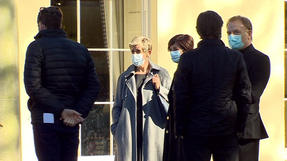The actors and crew stand around wearing masks