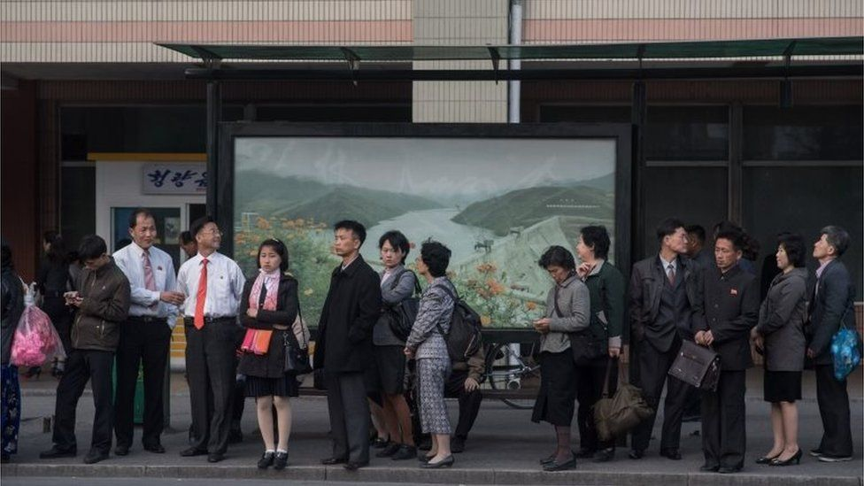 In a photo taken on April 13, 2017 commuters wait at a bus stop in Pyongyang