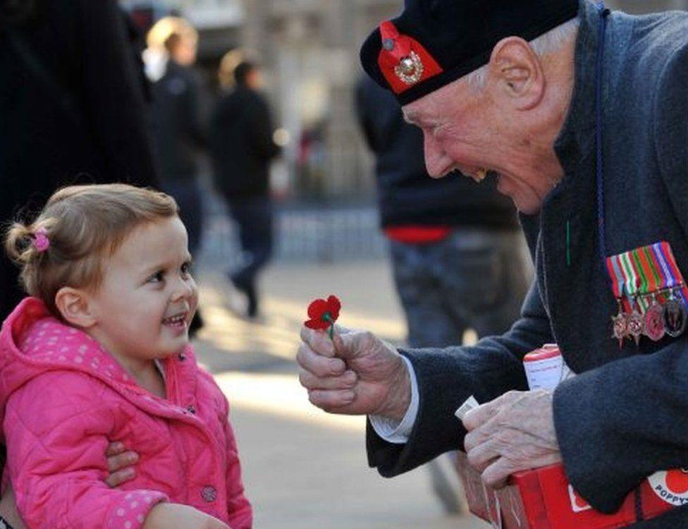Veteran giving child poppy