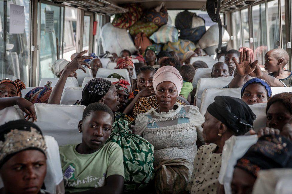People sit inside a bus.
