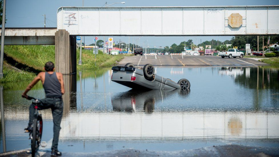 A man on a bicycle surveys an overturned truck in receding floodwater in Port Arthur, Texas