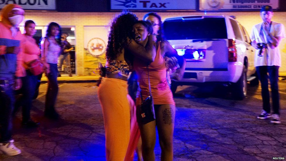 A woman reacts after shots were fired in a police-officer involved shooting in Ferguson, Missouri August 9, 2015