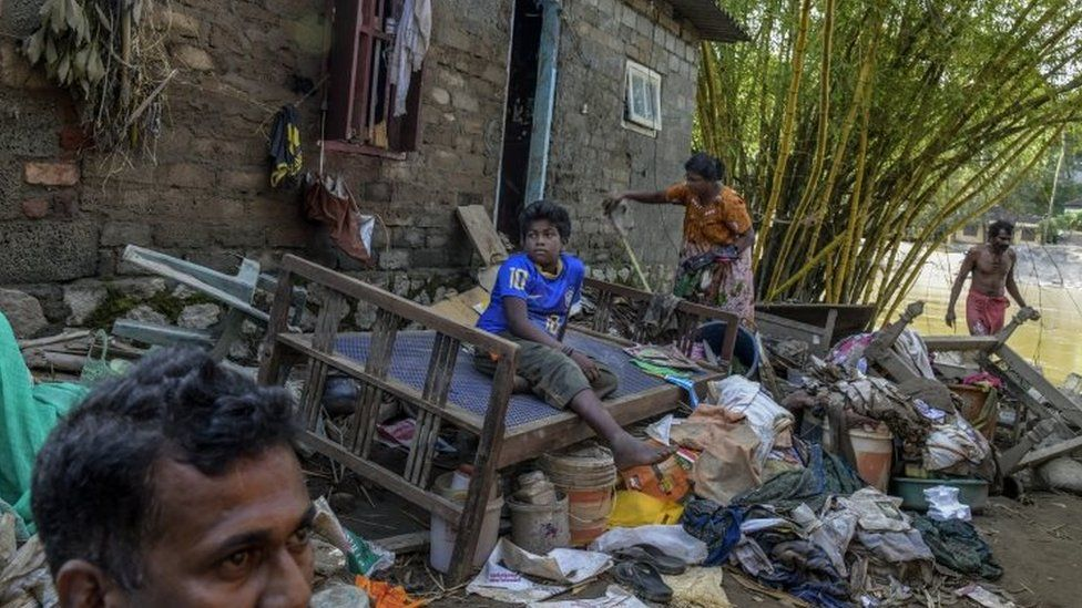 Sandhya Biji and her son in front of their damaged house on the banks of Pamba river in Mumndancava village after a flood on August 23, 2018 in Kerala, India