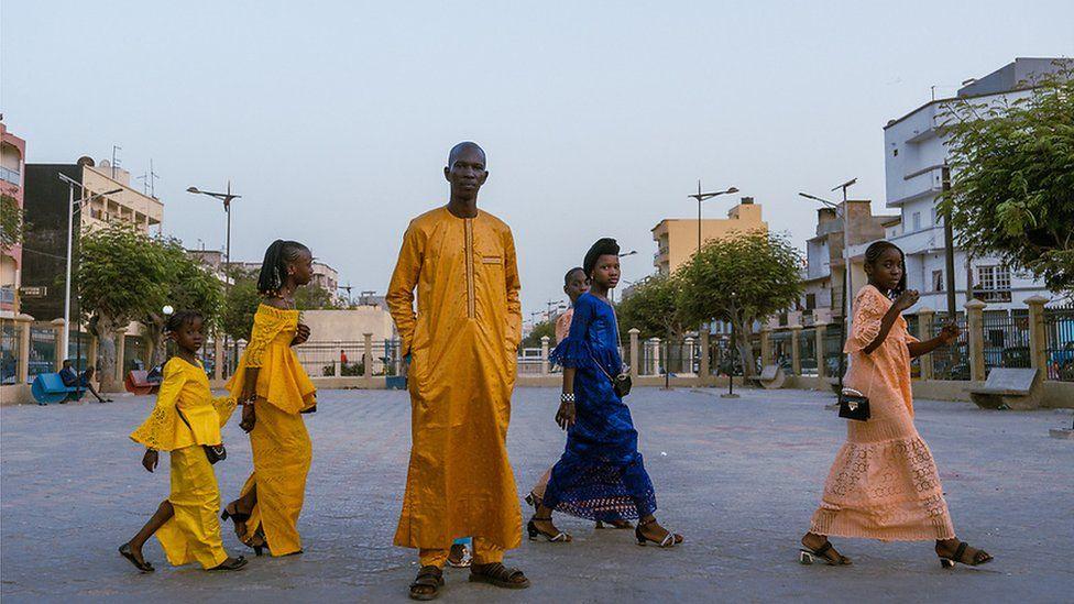 Taxi driver Fallou Sene poses for the camera in an orange boubou