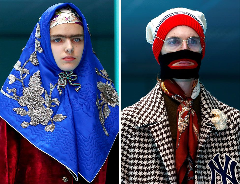 Two models on the catwalk, one wearing a bright blue headscarf with silver floral stitching and the other wearing a woolly hat, balaclava and glasses