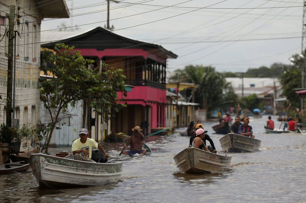 People pass on their boats through a street flooded by the rising Solimoes river