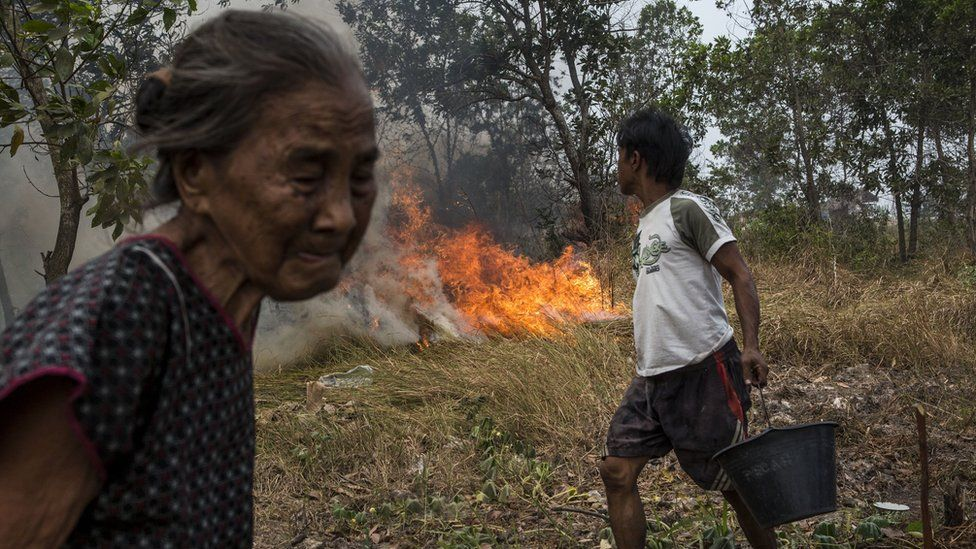 A man carries a bucket of water as people try to extinguish the fire on burned peatland and fields near his house in Palembang, South Sumatra, Indonesia